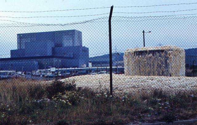 Ein altersschwacher Zaun vor dem Hauptgebäude des Kernkraftwerks Hunterston in Svchottland. Rechts quillt braune Flüssigkeit mit großen Blasen aus einem Betonrohr.