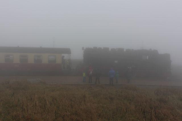 Eine Lok und ein Wagen der Bahn auf dem Brocken. Davor mehrere Personen im dichten Nebel.