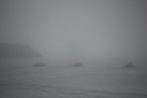 Drei kaum erkennbare Ruderboote in starkem Nebel.