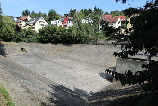Regenrückhaltebecken, komplett aus Beton. Im Hintergrund einige Häuser mit Gärten.