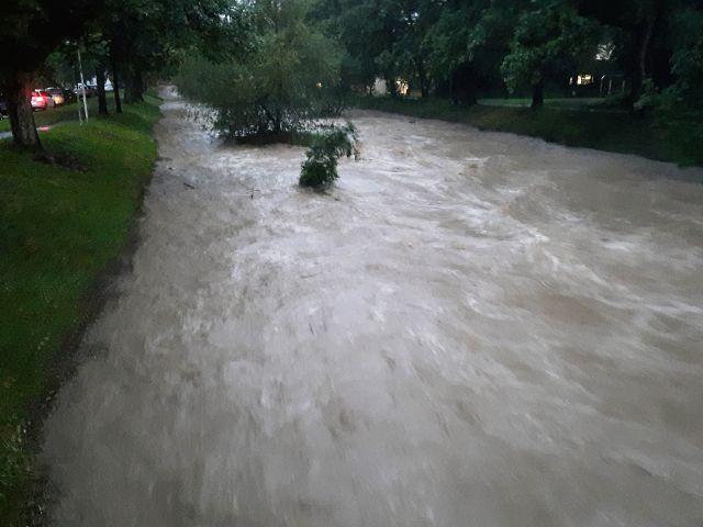 Ein kanalsierter Bach führt Hochwasser.