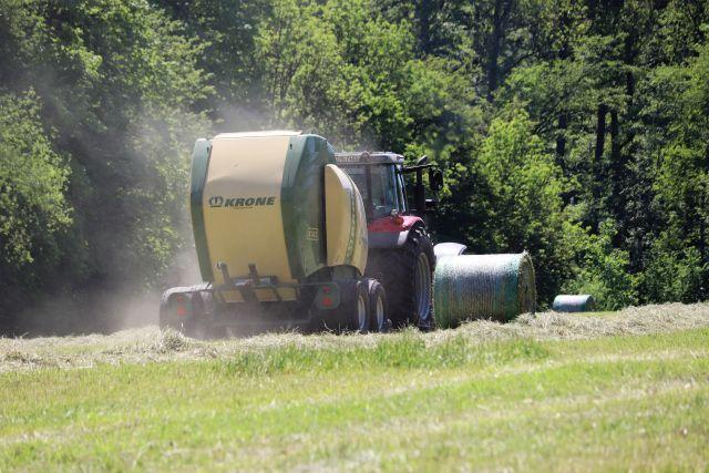 Traktor mit einem Anhänger, der Heu in Ballen presst auf einer gemähten Wiese.