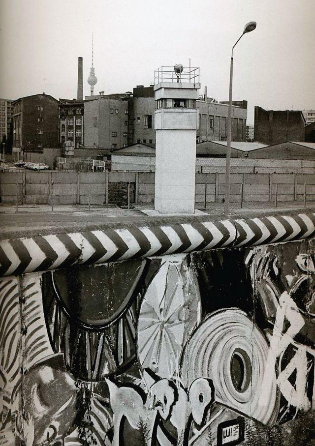 Beobachtungsturm der Grenztruppen der DDR, davor die Mauer.