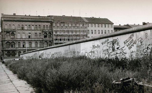 Die Berliner Mauer von westlicher Seite aus aufgenommen. Sie ist voll von Graffiti. Dahinter alte mehrstockige Mietshäuser.