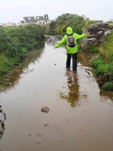 Eine Person mit grüner Regenjacke und kleinem braunen Rucksack stapft durch braunes Wasser auf einem Feldweg. Die Brühe reicht bis über die Wanderstiefel.