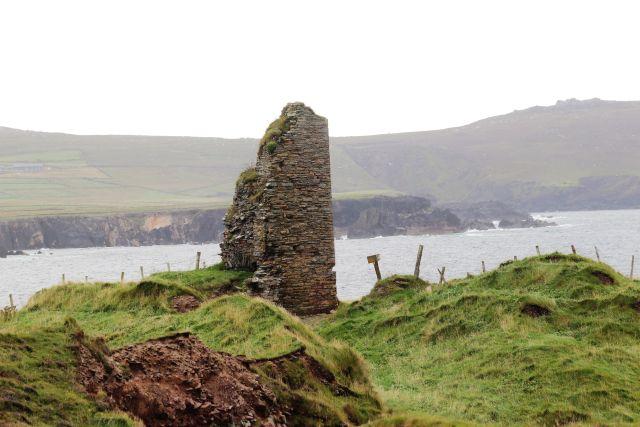 Ein aus Natursteinen errichteter Gebäudeteil eins ansonsten zerstörten Wohnturms. Im Hintergrund eine Meeresbucht.