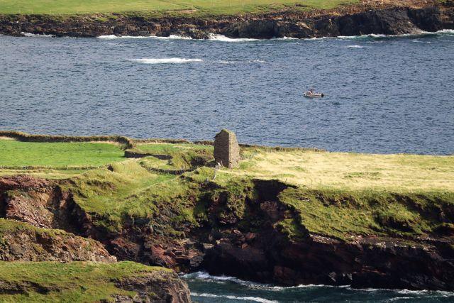 Blick von einem Berghang auf eine Landzunge. In der Mitte steht die Ruine von Ferriter's Castle. Zu sehen sind Erdwälle früherer Wallanlagen.