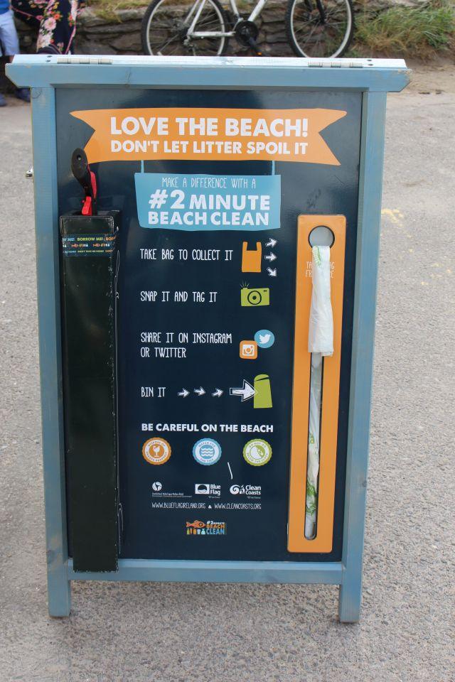 Hinweisschild zur Reinigung des Strands mit einer Zange und Säcken.