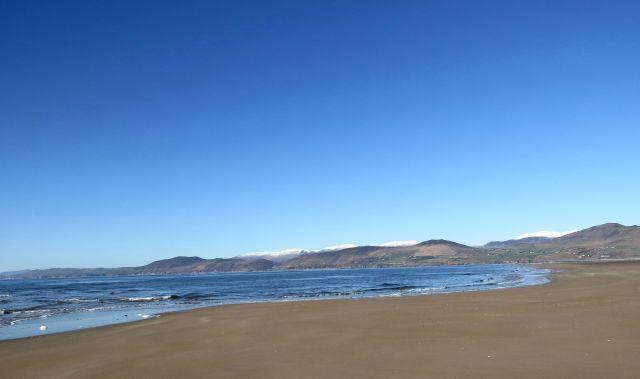 Menschenleerer Sandstrand im Winter. Im Hintergrund die die ersten Berge derDingle Halbinsel.