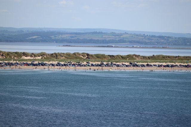 Im Vordergrund blaues Meer, dann eine Landzunge, dahinter wieder Meer. Auf der Landzunge stehen am hellen Sandsatrand zahlreiche Fahrzeuge vor den Dünen.