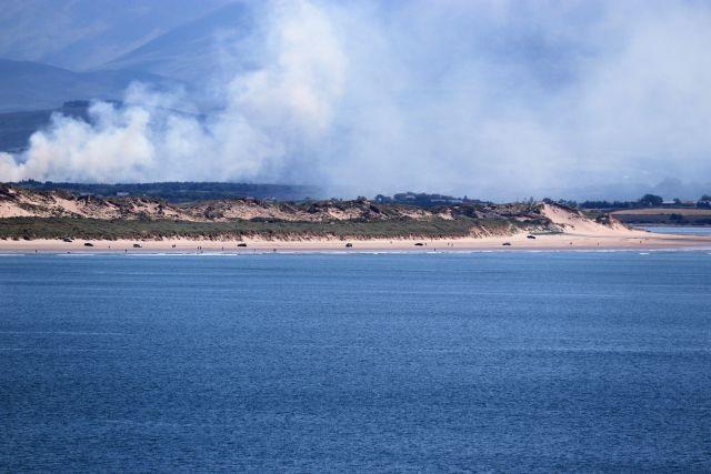 Das Ende einer Landzunge, die sich ins blaue Meer erstreckt. Einige Fahrzeuge am hellen Strand, dahinter eine Rauchwolke.