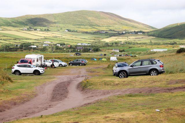 Wildes 'Campen' hinter einer Düne am Meer. Wohnmobil und andere Fahrzeuge stehen auf Sand und Gras.