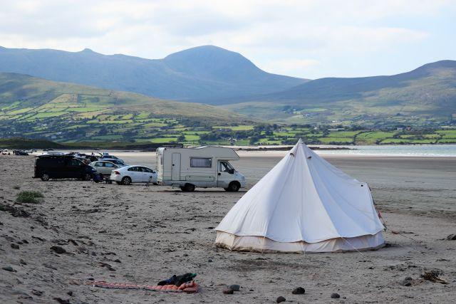 Ein großes, weißes Zelt - Tipi - im Vordergrund, dahinter ein Wohnmobil und weitere Fahrzeuge auf dem Sandstrand. Rechts das Meer. Im Hintergrund Berge.
