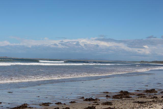Der Strand bei Inch im Winter. Strahlender Sonnenschein, die Wellen laufen auf. Der Sandstrand ist leer. Es liegt etwas Seetang dort. Die Wellen laufen sich weiß brechend auf.