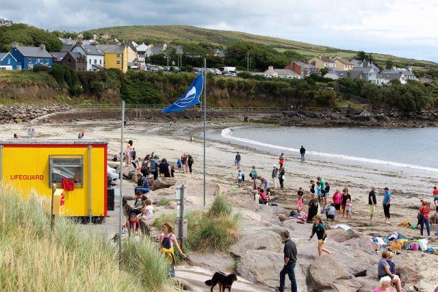 Strand in Ventry. Es weht die Blue Flag. Links die Station der Lifeguard. Zahlreiche Personen am Sandstrand. Im Hintergrund die Ortschaft Ventry.