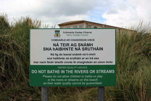 Hinweisschild an Ventry Beach, in englischer und irischer Sprache. Es wird dringend vom Baden an den Bachmündungen abgeraten.