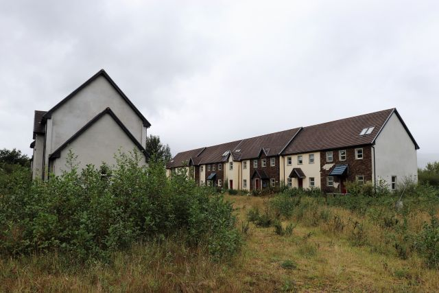 Ein Wohnquartier aus mehreren Reihenhäusern. Die Natur kehrt zurück, die Gebäude zeigen bereits wieder Schäden. Leerstand seit einem Jahrzehnt.