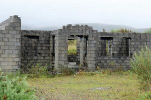 Bauruine aus hellen Betonsteinen. Es wurde nur ein Teil der Mauern erichtet, Gras und Büsche erobern den Platz zurück.