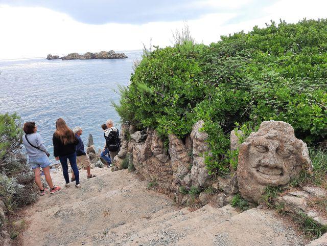 Aus dem Stein herausgearbeitete Figuren, dahinter eine grüne Hecke. Links Besucher und das Meer.