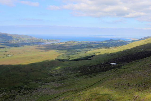 Blick vom Connor Pass in Richtung Brandon Bay. In der Landschaft gibt es Trockensteinmauern und kleine Seen. Unter blauem Himmel mit weißen Wölkchen liegt das Meer ruhig.