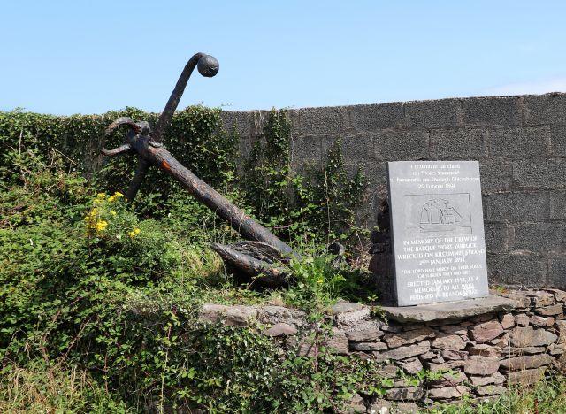 Ein großer rostiger Anker liegt hinter einer grauen Gedenktafel mit einem Text in irischer und englischer Sprache und einem Relief des Dreimasters. Erinnert wird an die Mannschaft der Port Yarrock.
