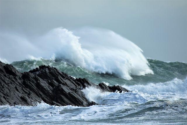 Hohe Wellen mit Gischt stürzen über Felsen auf den Strand.