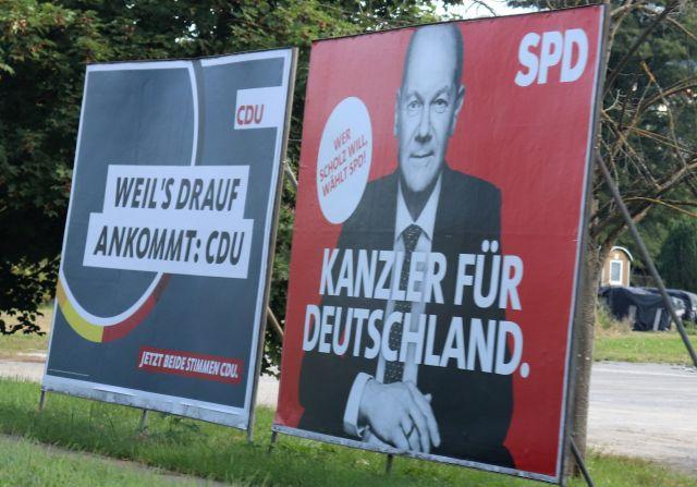 """Zwei Wahlplakate von CDU und SPD. Texte: """"Weil's drauf ankommt: CDU"""" und """"Wer Scholz will wählte SPD - Kanzler für Deutschland""""."""